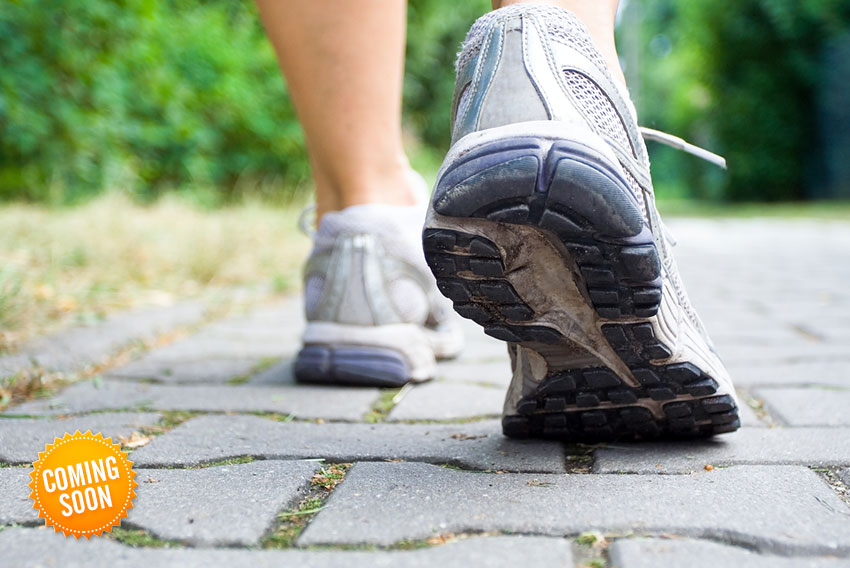 A close up of a person exercising outdoors - a pair of trainers close up on the heels.