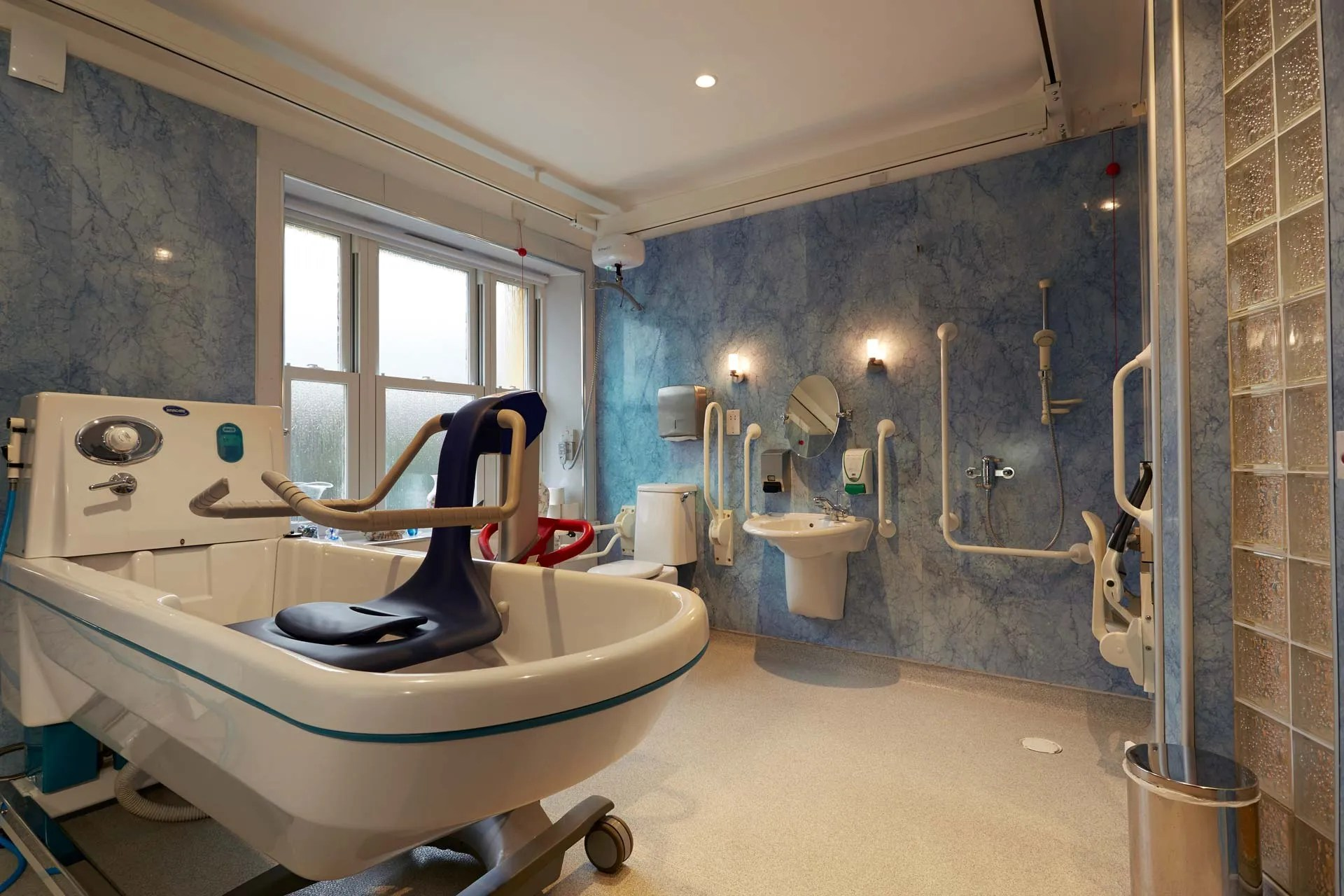 A fully kitted out bathroom for assisted bathing, with accessible bathtub and shower.
