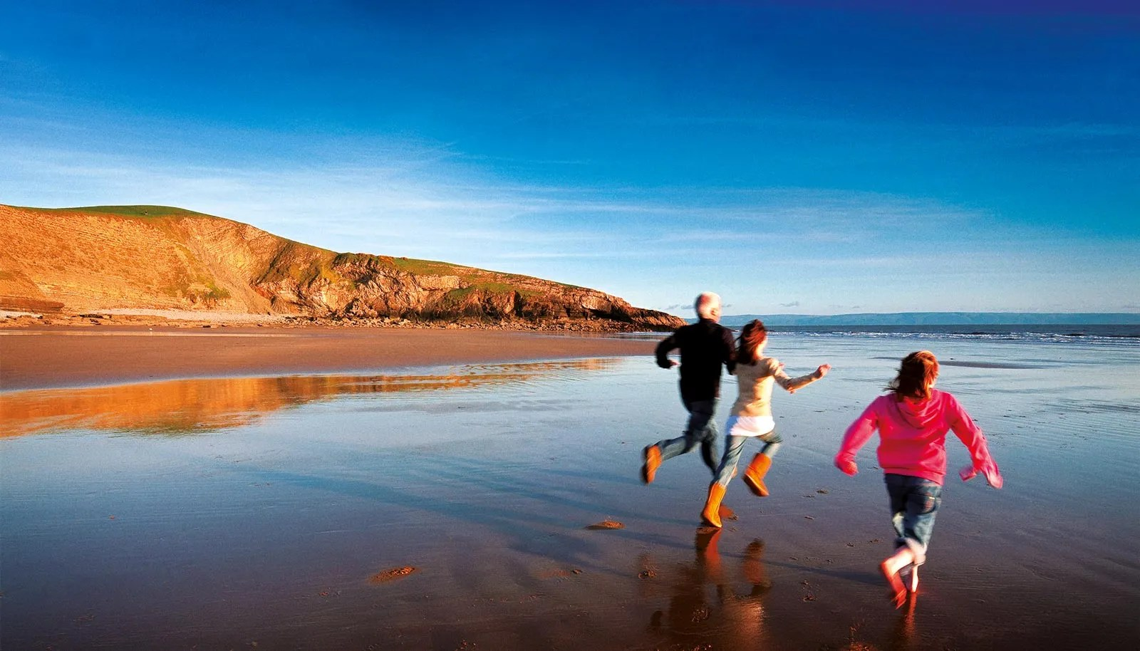 A family running on the beach towards the waves in Wales