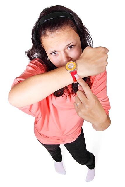Fru zeigt auf Ihre Armbanduhr, hier Verzögerung