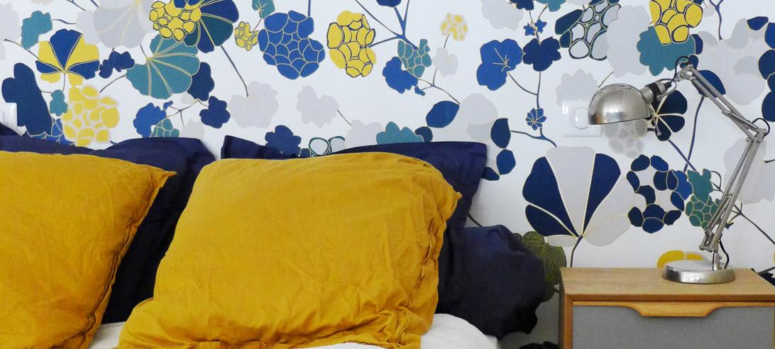 Réalisation du studio d'architecture et de décoration Skéa Designer. Projet réalisé dans le cadre d'une prestation d'architecture d'intérieur rénovation et de décoration. Vue d'une chambre avec papier peint floral et draps unis. Jaune curry, bleu électrique et beige sable.