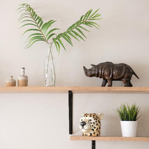 Un vase en forme de tête de léopard, une enceinte Marshall et une famille de Rhinocéros décorent les étagères murales.