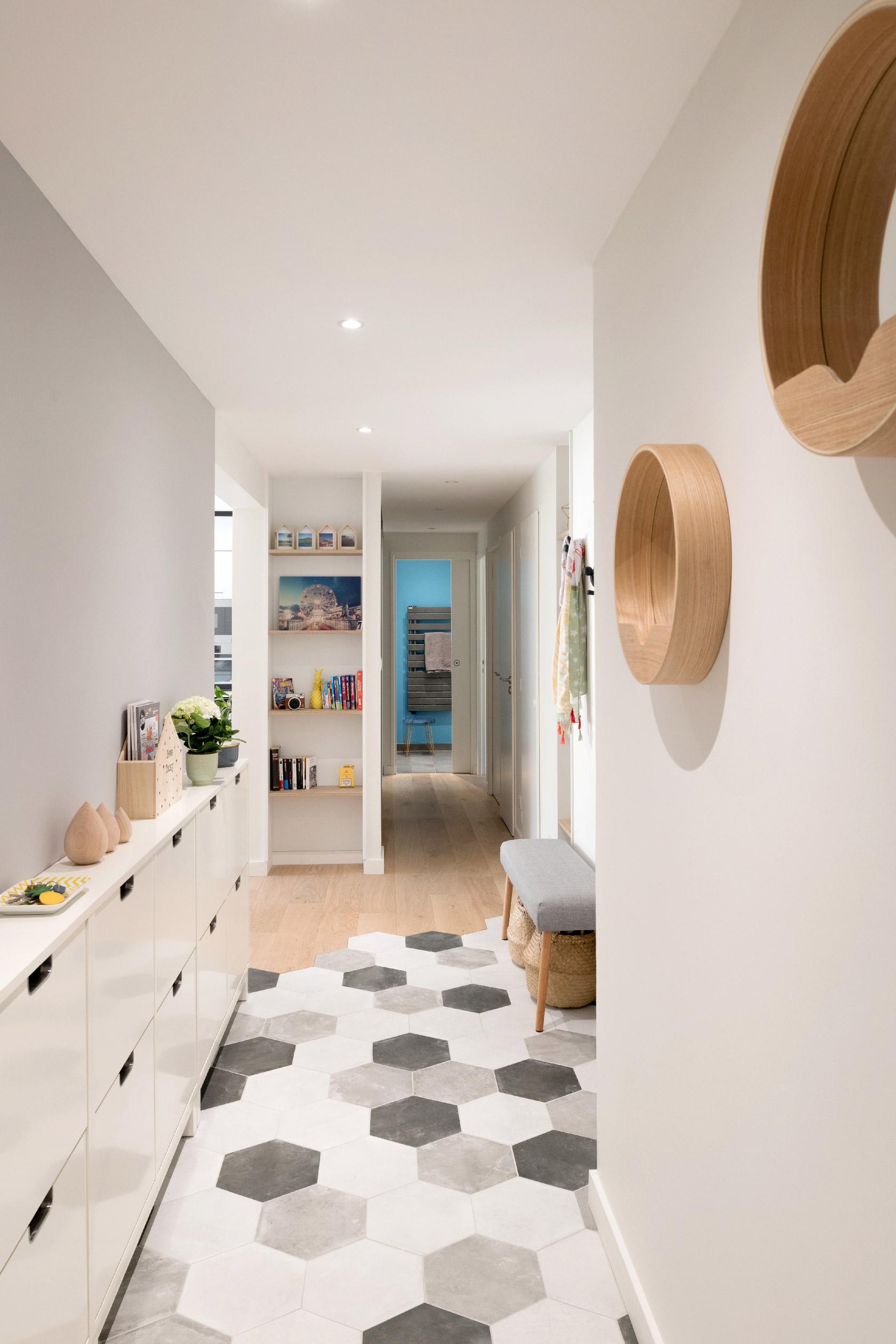 Un couloir d'entrée avec un rangement à chaussures. Au sol, un carrelage hexagonal imite des carreaux de ciment blancs, gris et noir. A la jointure, la découpe du parquet suit la forme du carrelage hexagonal.