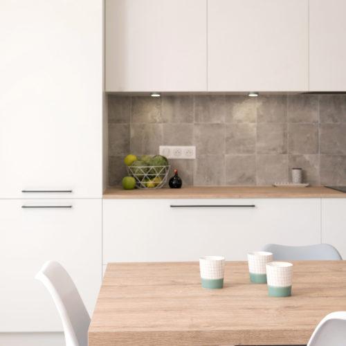 Derrière la table en bois et les chaises de cuisine, un plan de travail en carrelage imitant un carreaux de ciment en béton gris est entouré de façades blanches avec des poignées noires. Une cuisine de charme ultra contemporaine.