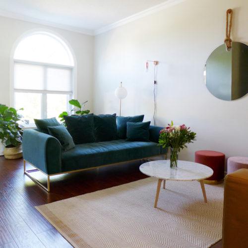 Réalisation du studio d'architecture et de décoration Skéa Designer. Velouté. Un canapé en velours bleu et son piétement métallique accompagnent une table basse en marbre et un tapis en fibre végétale.
