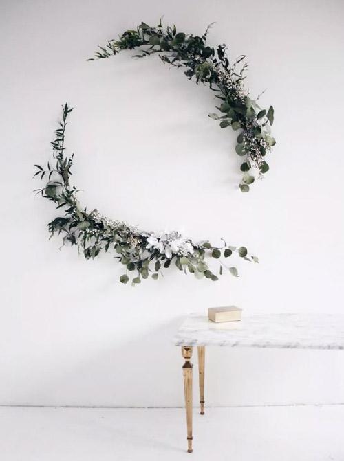 Inspiration. Couronne d'eucalyptus. Vue d'une couronne d'eucalyptus placée en deux pans distincts et arrondis sur un mur blanc. Très épuré.