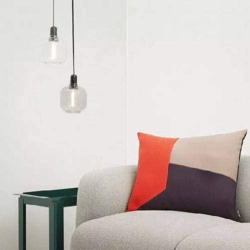 Eclairage. Luminaires en grappe. Deux luminaires en grappe tombent à côté d'un fauteuil.