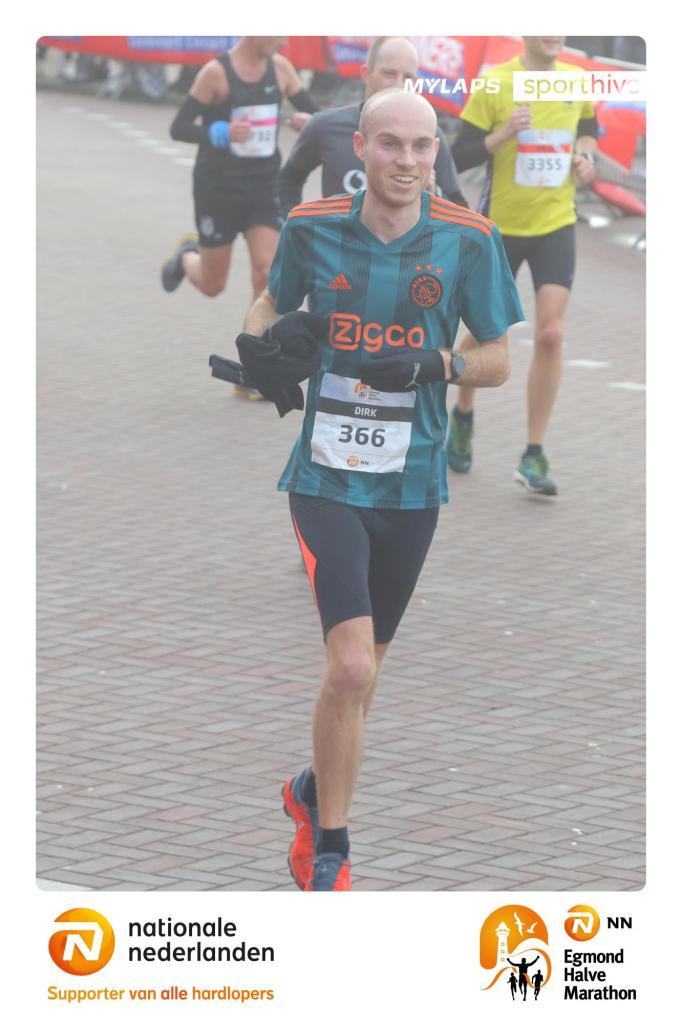 Skedel op weg naar de finish tijdens de halve marathon van Egmond, met thermoshirt in de hand