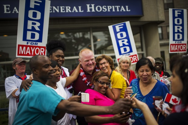 Toronto Mayor Rob Ford poses with members of the public as he takes part in the East York Canada Day Parade in his first public appearance since returning from a rehabilitation clinic for substance abuse problems in Toronto in this July 1, 2014, file photo. Ford, the former mayor of Toronto who gained global notoriety for admitting to smoking crack cocaine while in office, died from cancer on March 22, 2016, his office said in a statement. REUTERS/Mark Blinch/Files