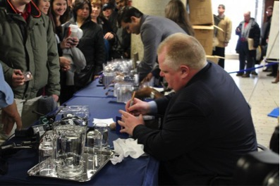 Mayor Ford signs bobble heads as onlookers wait for a chance to buy their own and have their picture taken with him.