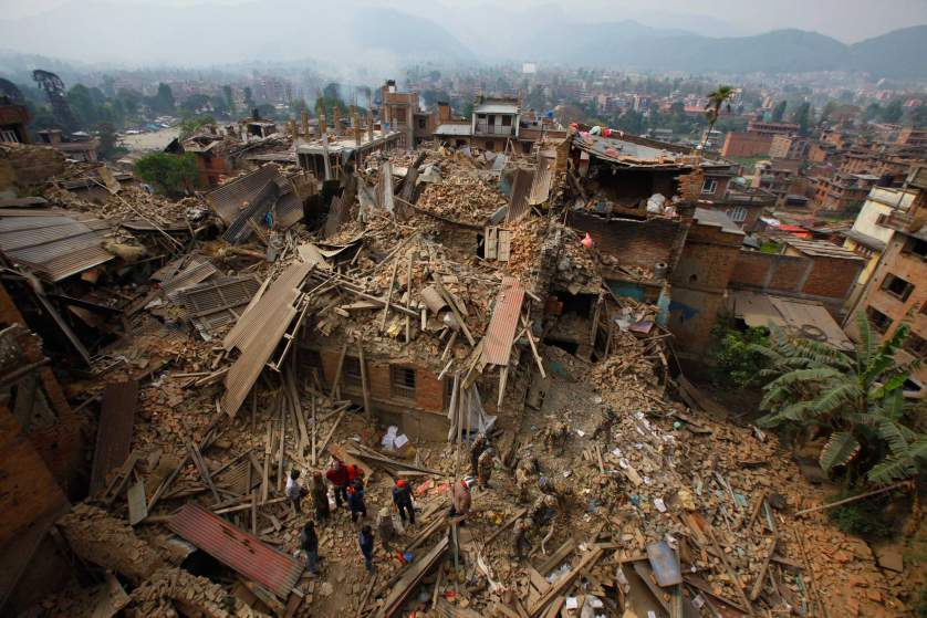 Rescue workers remove debris as they search for victims of earthquake in Bhaktapur near Kathmandu, Nepal, Sunday, April 26, 2015. A strong magnitude earthquake shook Nepal's capital and the densely populated Kathmandu Valley before noon Saturday, causing extensive damage with toppled walls and collapsed buildings, officials said. (AP Photo/Niranjan Shrestha)
