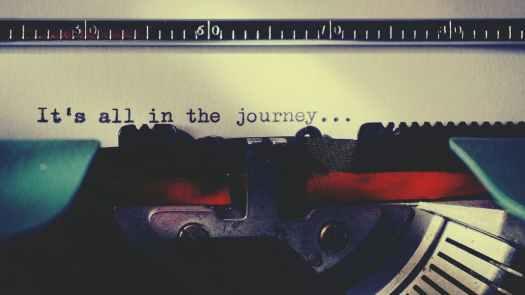 black typewriter machine typing on white printer paper
