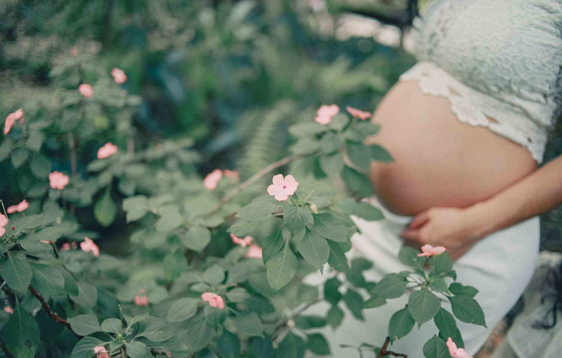 pregnant standing near the flower