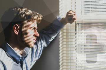 A man in a blue shirt looking out of a window whilst contemplating.