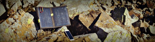 Portable Solar Panel Charging A Phone On Large Rocks