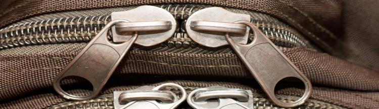 Closeup view of closed zippers on a bag.