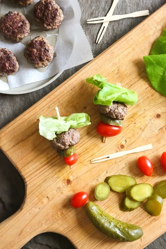 Mini burgers with bacon, layered on a bamboo skewer with lettuce, tomatoes and pickles! Who can resist your favorite foods on a stick – not me! These burger bites make the perfect low-carb appetizer to please everyone from age six to age sixty, just set out some ketchup and mustard for dipping and watch them disappear.