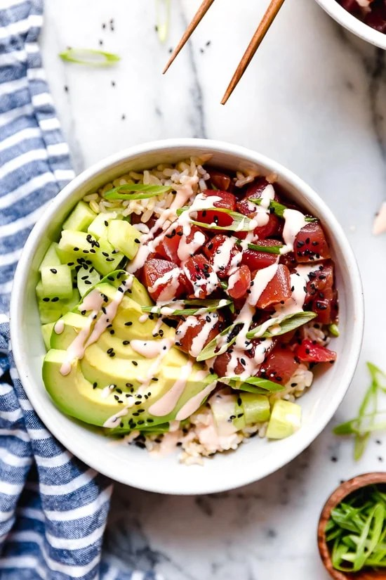 Poke Bowls made with chunks of fresh tuna, avocado, cucumbers, spicy mayo, scallions cut on the bias served on a bed of steamed rice.