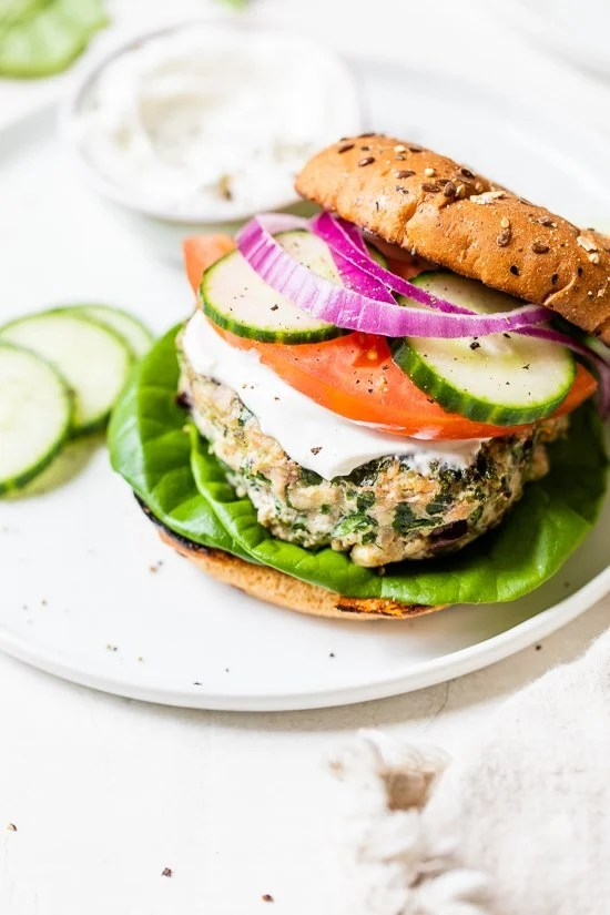 Greek turkey burger with bun, tomatoes, cucumber on a plate