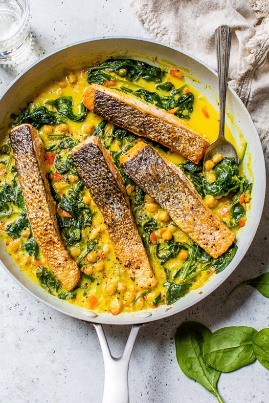 salmon in a skillet with spinach and chickpeas