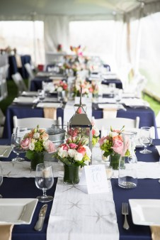 The tables looked beautiful with navy satin linens, starfish table runners and flowers & lanterns by Fancy Flowers by Meredith. Table cards by SKO Designs. Photography by Organic Photography.