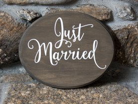 "Stained wooden oval ""Just Married"" sign with glossy white vinyl lettering. Initials or names can be added at the bottom to personalize."