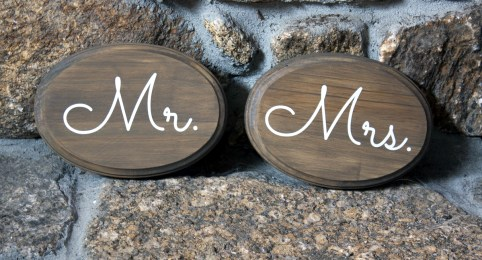 Oval stained wood Mr. & Mrs. chair signs with white glossy vinyl lettering.