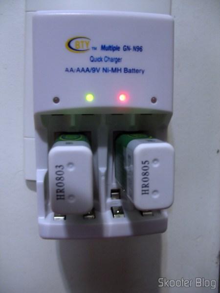 DealExtreme: Carregador Rápido Inteligente 4 Canais Auto-Stop para baterias AA/AAA/9V 6F22 BTY (100~240V AC): a luz verde indica que a bateria à esquerda já está totalmente carrega, a da direita ainda está carregando