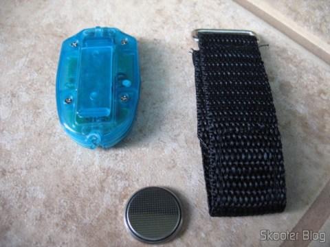 A parte de trás do aparelho com o clipe, ao lado da braçadeira e da bateria CR2032