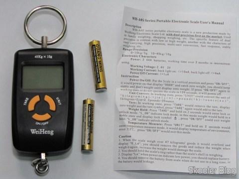 A balança, um par de pilhas AAA e o manual de instruções em inglês (e chinês no verso)
