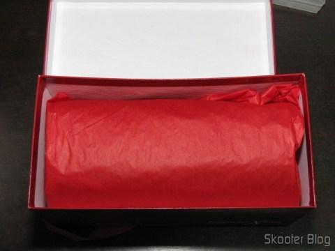 A embalagem original do perfume vem embrulhada com papel de seda vermelho, dentro da caixa de presente da FragranceX.com