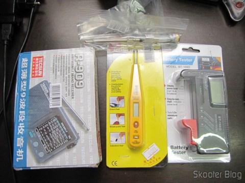 """O Rádio Portátil Tecsun R-909 Multibanda com 9 faixas FM / AM / SW (7 faixas de ondas curtas, 2 x AA), a Chave de Fenda com Teste de Voltagem c/ LCD AC/DC 12~250V, a Chave de Fenda de Bolso com Teste de Voltagem AC 100-500V, e o Testador Digital de Carga de Pilhas/Baterias com LCD de 3.5"""""""