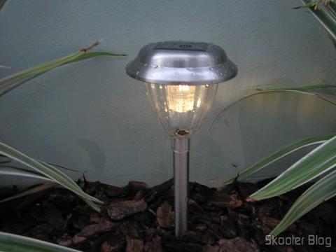 Lâmpada de Jardim de Aço Inoxidável com Luz de LED Branca Auto-Recarregável com Energia Solar (1*AA) (Stainless Steel Solar Powered Self-Recharged LED White Light Lawn Lamp (1*AA)) instalada e em funcionamento à noite. Luz amarela nessa nova remessa.