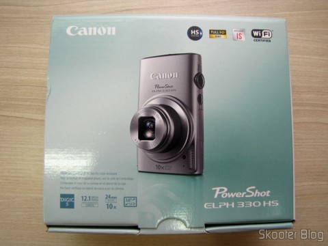 Câmera Digital Canon PowerShot ELPH 330 HS 12.1 MP Wi-Fi CMOS Zoom Óptico 10X Lentes 24mm Video Full HD 1080p (Canon PowerShot ELPH 330 HS 12.1 MP Wi-Fi Enabled CMOS Digital Camera with 10x Optical Zoom 24mm Wide-Angle Lens and 1080p Full HD Video (Black)), em sua embalagem