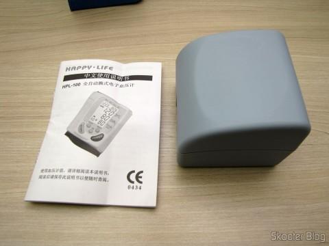 Monitor de Pressão Arterial de Pulso Totalmente Automático Happy Life HPL-100, em seu estojo, ao lado do manual de instruções