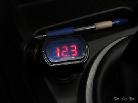 Medidor de Tensão de Bateria Automotiva com display LED e Conector para Tomada de Acendedor de Cigarros, em funcionamento, com o motor do carro desligado
