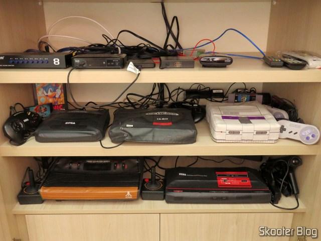 Consoles de videogames instalados na TV CRT, com suas respectivas capas.