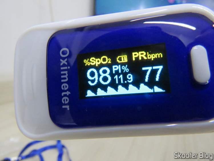 Oxímetro de Dedo OLED em Inglês e Português, em funcionamento.