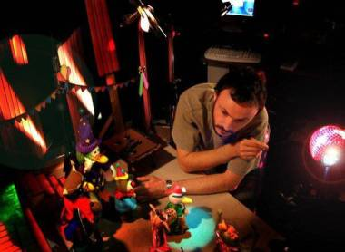 Photo: Christine Vestergaard. Still from 'Hana's Helpline' (Calon). Sometimes as an animator you will be expected to work with a number of puppets, as animator Ben is doing here. The skill is knowing sometimes how little to move something - a really key thing to understand in crowd scenes.