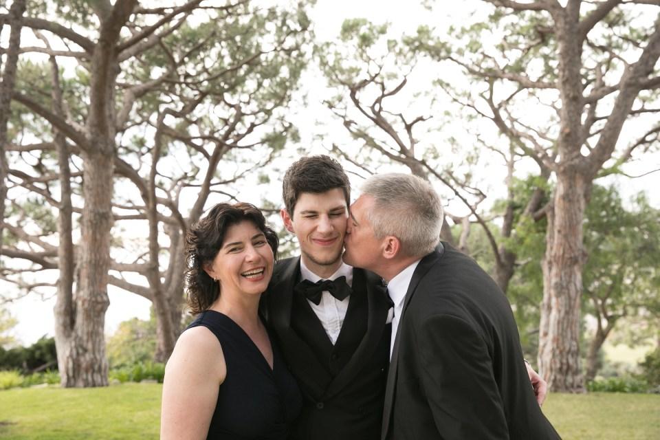 mom and dad kiss groom on wedding day