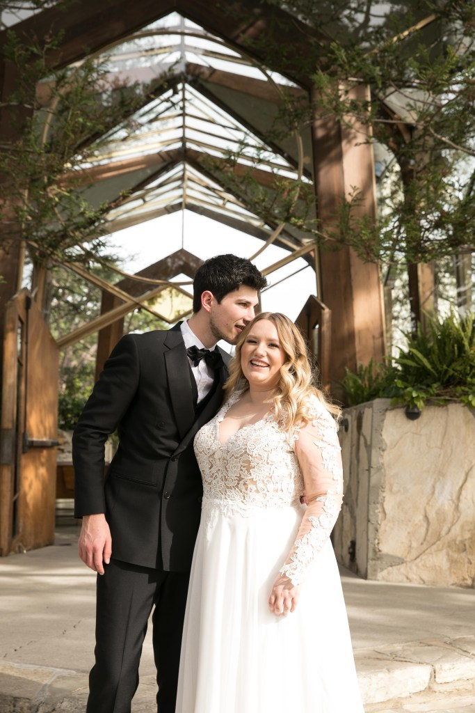 husband and wife photographed in front of glass chapel
