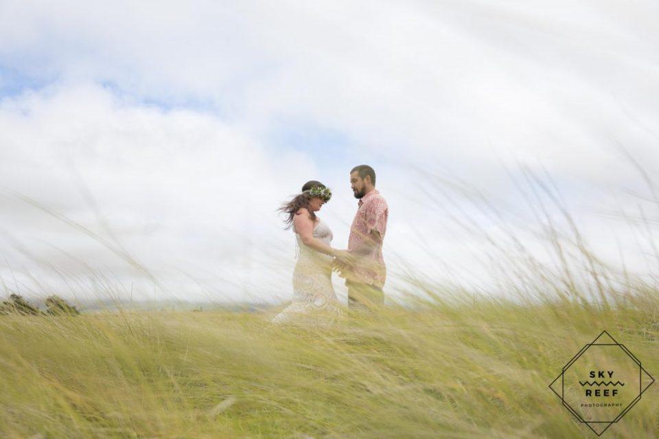 Bride and groom take photo in field in Waimea
