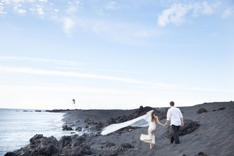 bride and groom hold hands along the beach after elopement