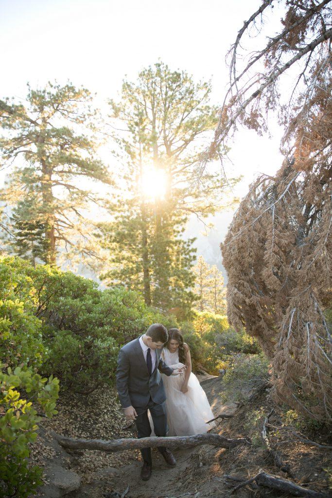 groom helps bride up hill Yosemite