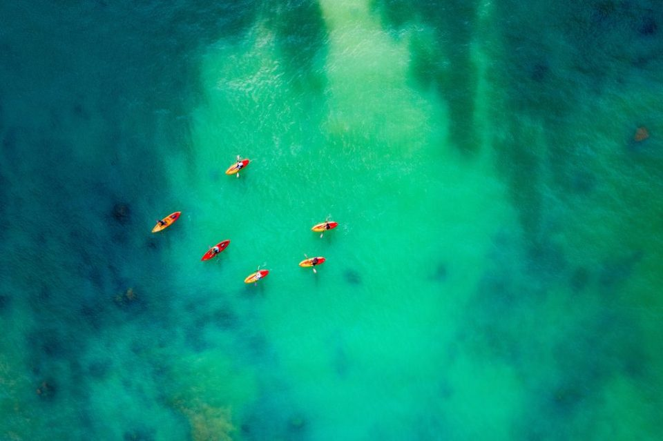 drone kayakers over ocean