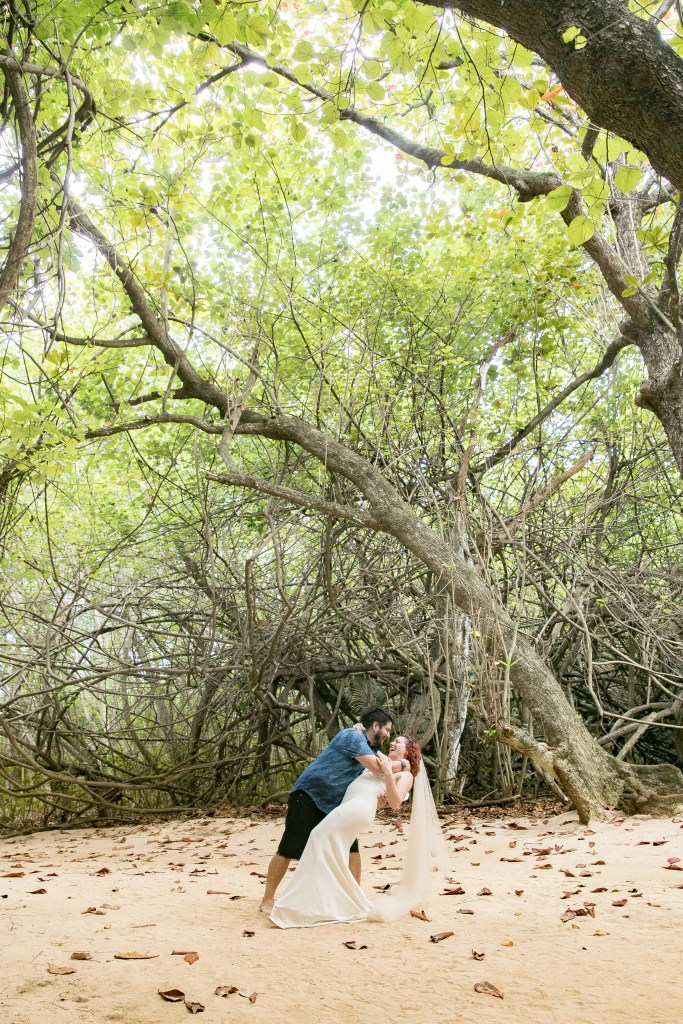 couple kiss under trees at wedding