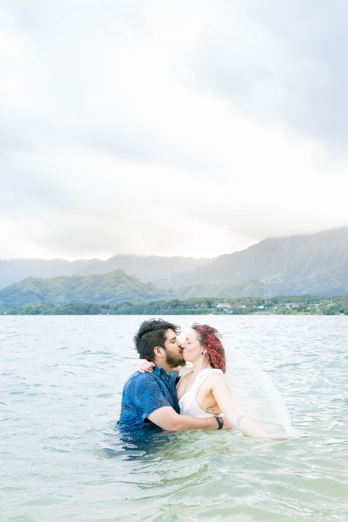 husband and wife kiss in ocean after Kualoa Secret Island Beach