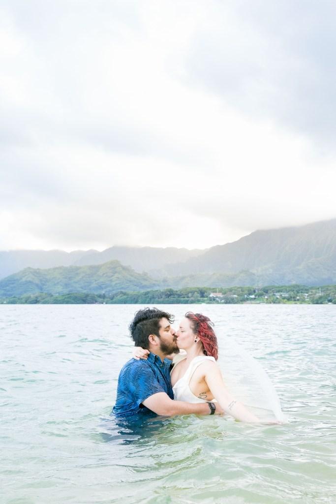 husband and wife kiss in ocean after Kualoa Secret Island Beach