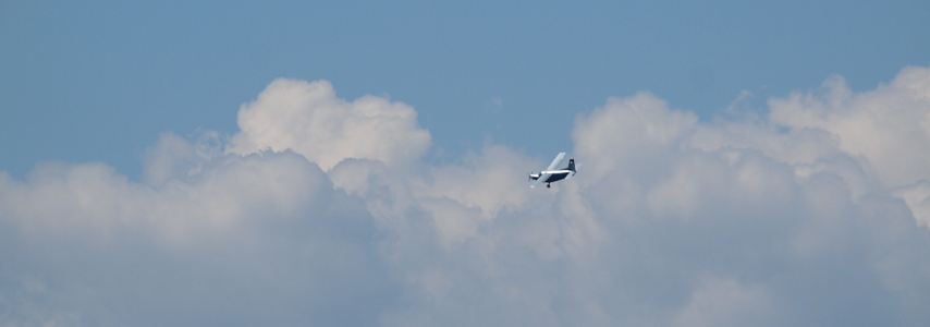 Flying airplane, clouds in background