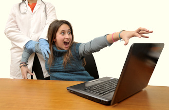 Young woman being dragged away from her laptop computer, as she tries to hang on to it.